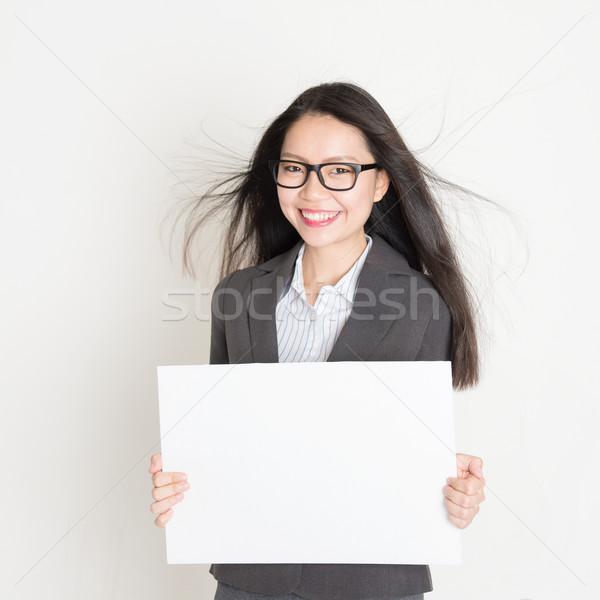 Asian business woman holding a blank placard Stock photo © szefei