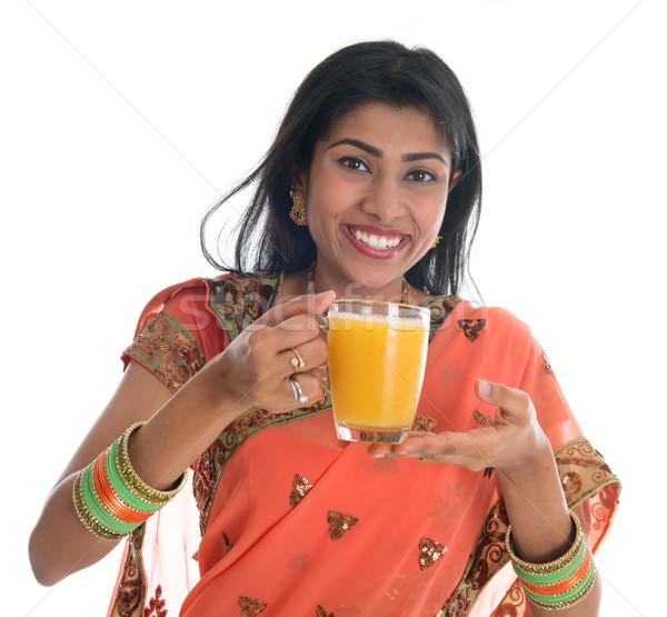 Indian woman in sari drinking orange juice Stock photo © szefei