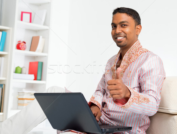 Indian man using computer at home. Stock photo © szefei