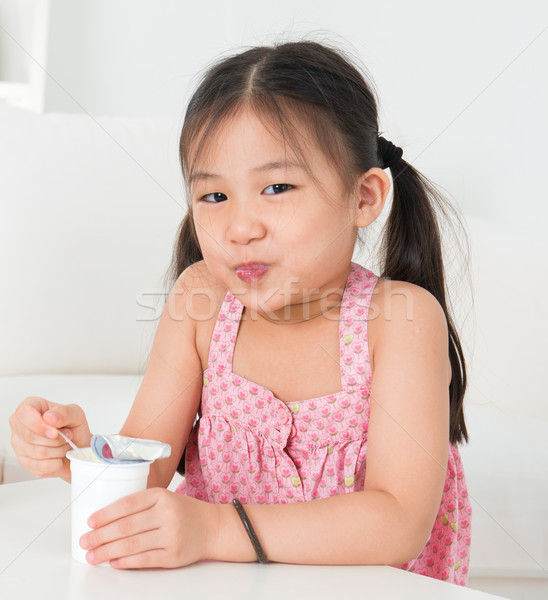 Asian kid eating yoghurt  Stock photo © szefei