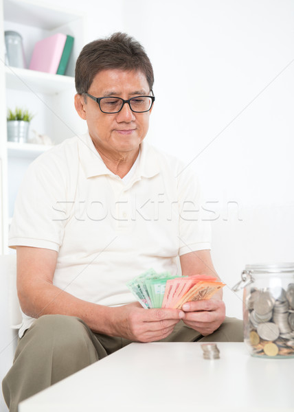 Mature Asian man counting money Stock photo © szefei