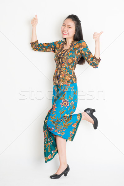 Asian girl thumbs up and jumping around Stock photo © szefei