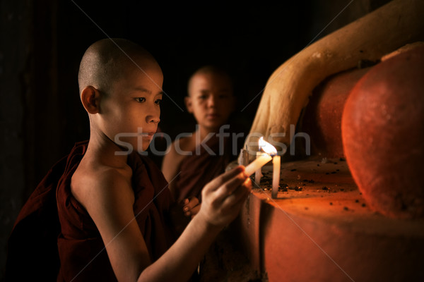 Buddhist novices praying with candlelight in monastery  Stock photo © szefei