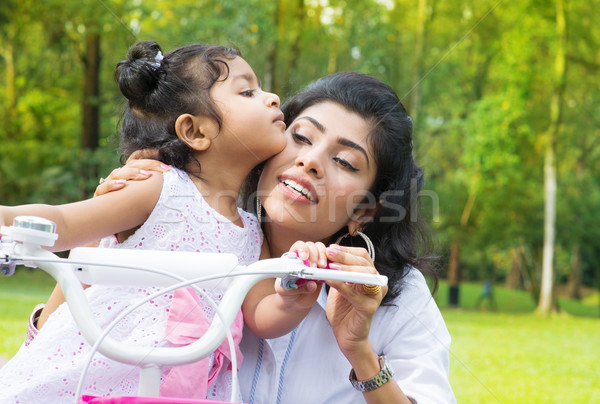 Indian mother teaching daughter cycling at the park Stock photo © szefei