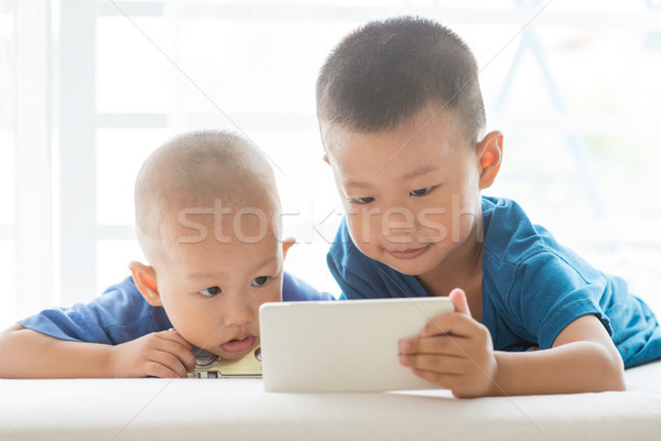 Young boys addicted to smart phone. Stock photo © szefei