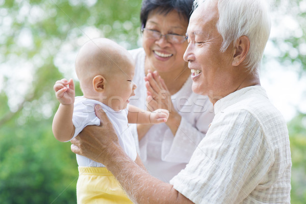 Asian grandparents playing with grandson Stock photo © szefei