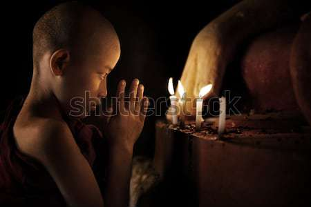 Buddhist novice with candlelight Stock photo © szefei