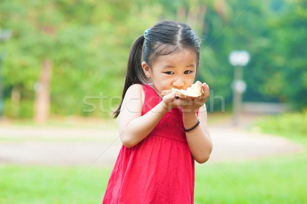 Alimentação sanduíche pequeno asiático menina ar fresco Foto stock © szefei