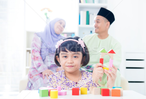 Muslim child building toy wooden house. Stock photo © szefei