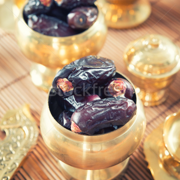 Dates fruit or kurma in metal bowl. Stock photo © szefei