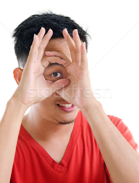 Asian man peeping through fingers hole Stock photo © szefei