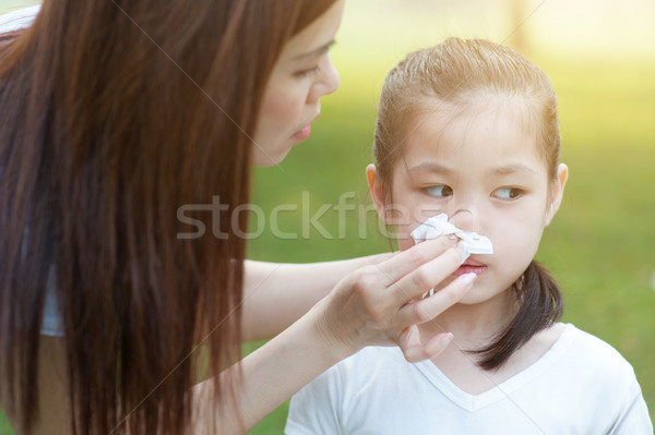 Flu season, little girl blowing nose. Stock photo © szefei