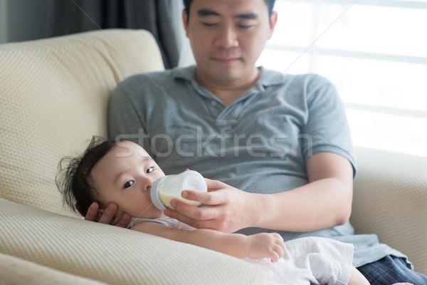 Father bottle feed milk to baby. Stock photo © szefei