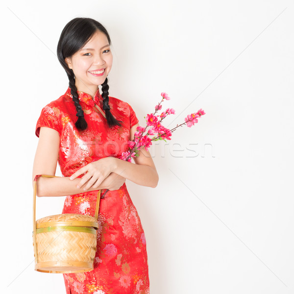 Oriental woman in red cheongsam holding gift basket Stock photo © szefei