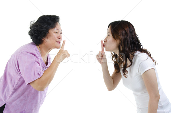 Mother and daughter finger on lips Stock photo © szefei