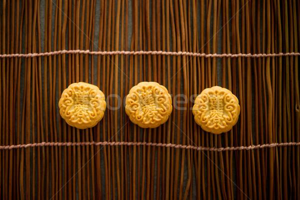 Moon cakes on bamboo mat with copy space dark light Stock photo © szefei