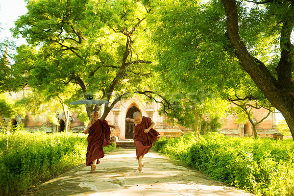 Young Buddhist novice monks running outside monastery Stock photo © szefei