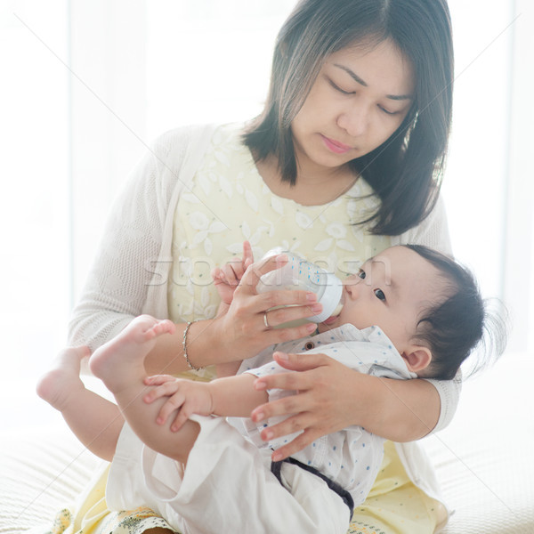 Father bottle feed milk to child. Stock photo © szefei