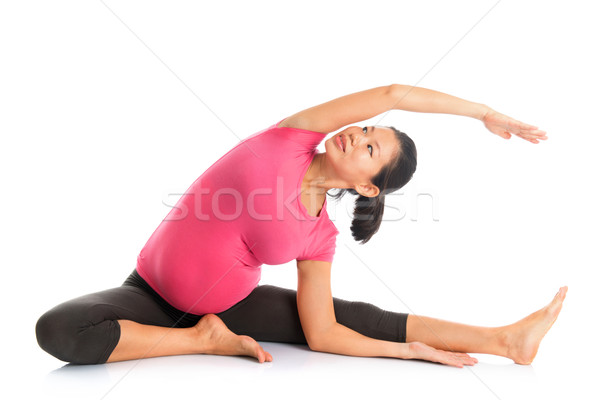 Pregnant woman yoga position seated side stretch. Stock photo © szefei