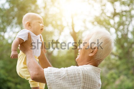 Grandfather with grandson sitting at outdoor bench. Stock photo © szefei