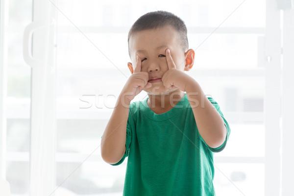 Playful boy pulling face Stock photo © szefei