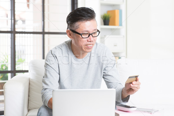Asian man making online payment Stock photo © szefei