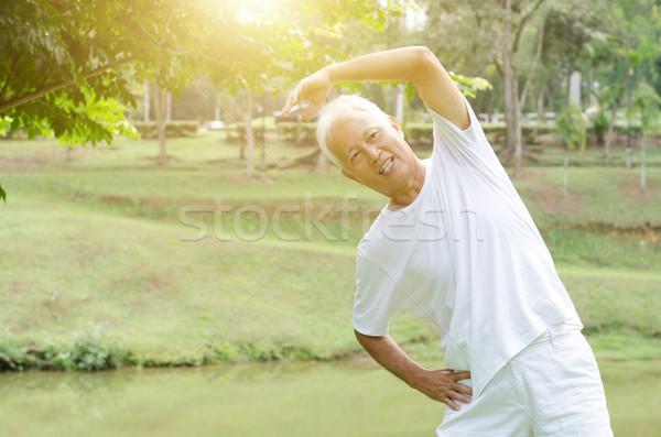 Senior man stretching outdoor  Stock photo © szefei