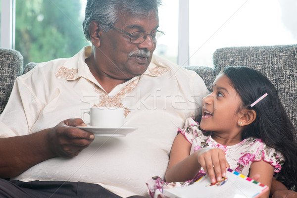 Granddaughter and grandfather reading book together Stock photo © szefei