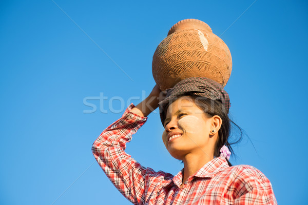Young Asian traditional farmer carrying clay pot on head Stock photo © szefei