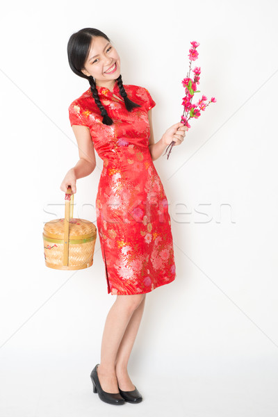 Oriental female in red qipao holding gift basket Stock photo © szefei