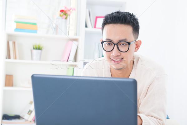 Délkelet ázsiai férfi online notebook otthon Stock fotó © szefei