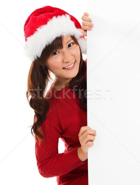 Christmas girl peeking from behind blank sign billboard.  Stock photo © szefei