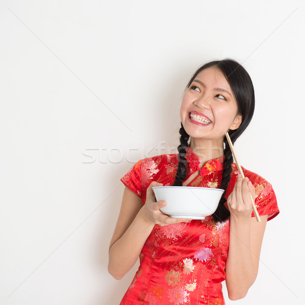 Asian chinese girl eating and looking up Stock photo © szefei