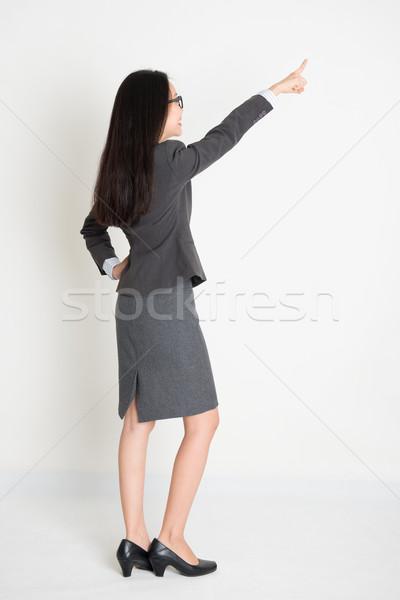 Full body backside Asian business woman pointing Stock photo © szefei