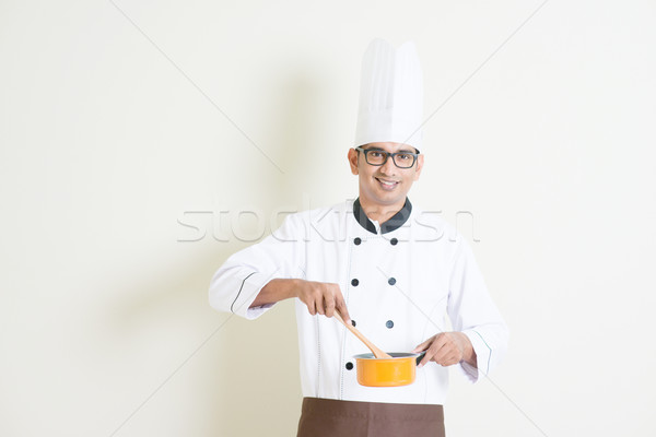 Indian male chef in uniform cooking food Stock photo © szefei
