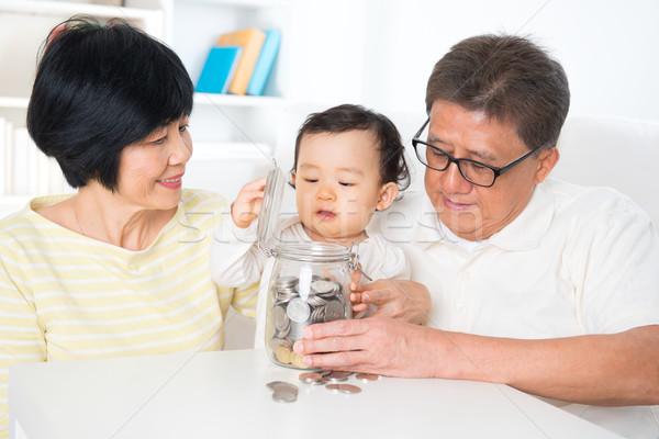 Asian familie besparing munten geld Stockfoto © szefei
