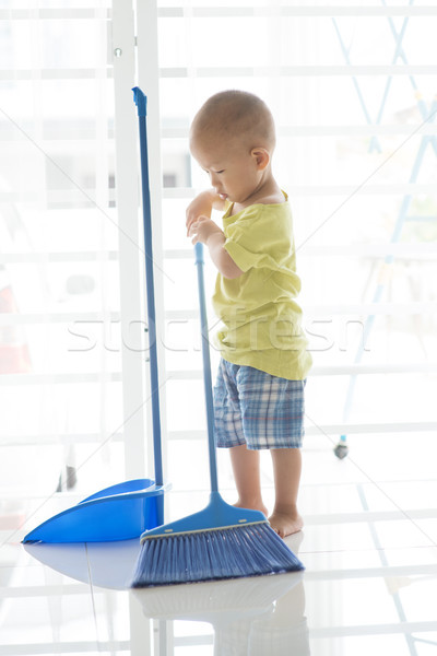 Young kid sweeping floor Stock photo © szefei