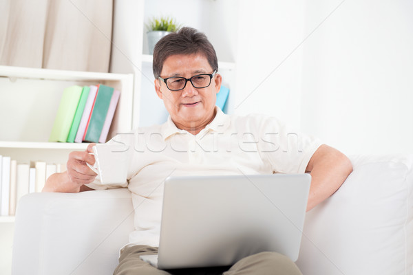 Mature Asian man surfing internet Stock photo © szefei