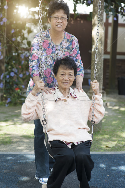 Asian senior adult women playing swing at outdoor playground Stock photo © szefei