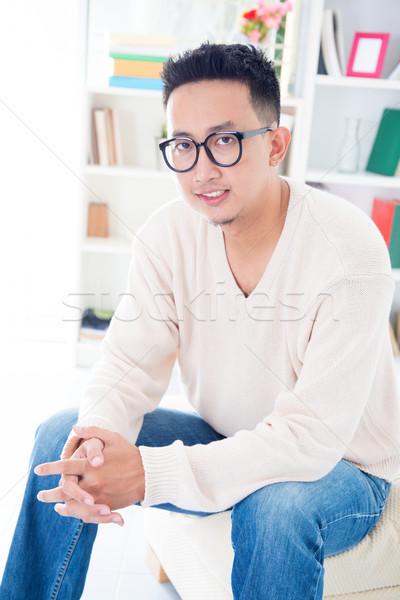 Délkelet ázsiai férfi szemüveg ül kanapé Stock fotó © szefei