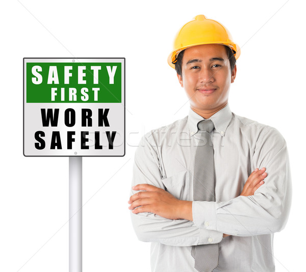 Asian male wearing yellow hardhat with safety first sign board. Stock photo © szefei