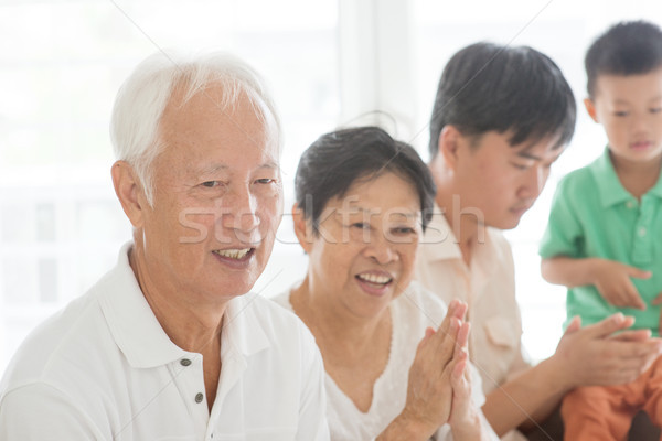 Happy Asian family clapping hands at home Stock photo © szefei