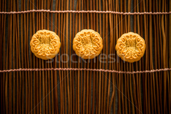 Moon cakes on bamboo mat with copy space low light Stock photo © szefei