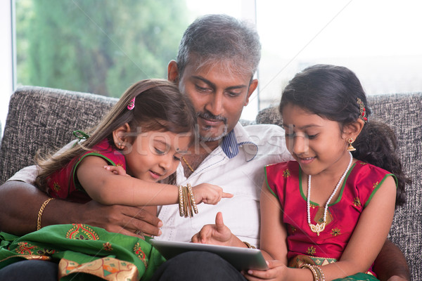 Indian family using tablet computer. Stock photo © szefei