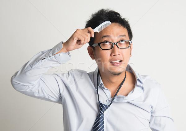Asian businessman combing hair  Stock photo © szefei