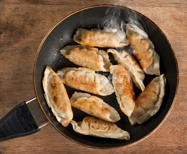 Asian dish fried dumpling in cooking pan Stock photo © szefei