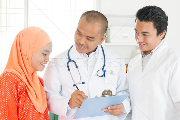 Medical doctor showing health report to patient. Stock photo © szefei