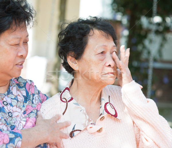 Sadness senior woman wiping off her tears Stock photo © szefei