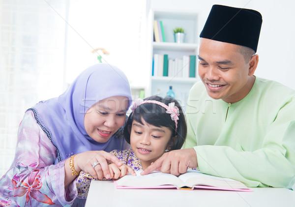 Muslim family reading book Stock photo © szefei