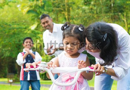 Stock photo: Indian  mother teaching little girl to ride a bike